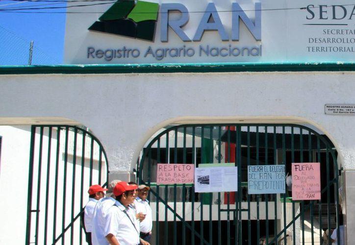 Imagen de las puertas del Registro Agrario donde diversos trabajadores colgaron carteles con demandas en contra del delegado local. (Milenio Novedades)