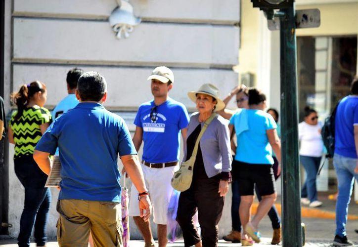 Se prevé cielo mayormente despejado con altas temperaturas. Imagen de contexto de un grupo de ciudadanos y turistas caminando en el Centro histórico de Mérida. (Milenio Novedades)
