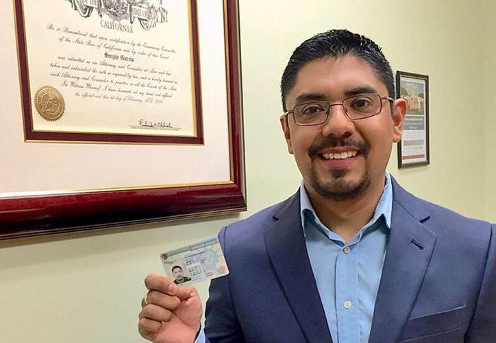 El mexicano Sergio García muestra orgulloso la tarjeta que lo acredita como residente en Estados Unidos. Gracias a ese documento, podrá ejercer como abogado luego de varios años enfrascado en una disputa legal. (AP)
