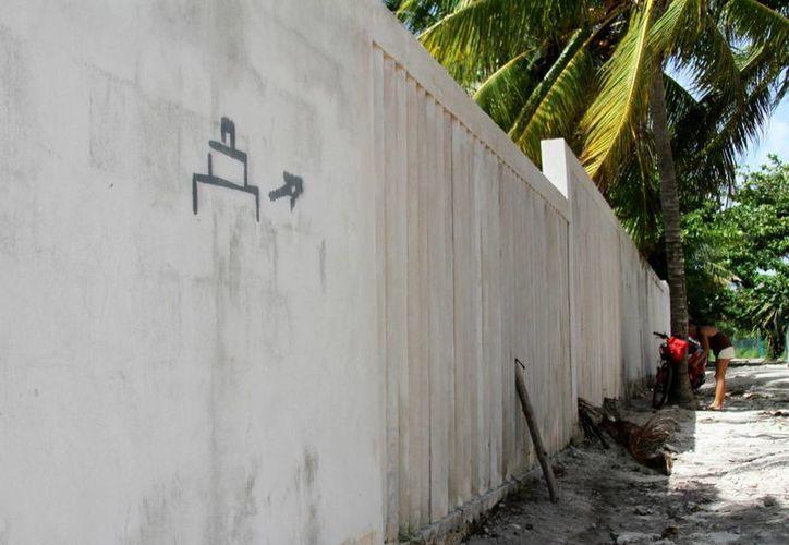 El camino para llegar a la zona arqueológica Xcalacoco está dotado únicamente de este dibujo que indica hacia dónde caminar para llegar.  (María Mauricio/SIPSE)