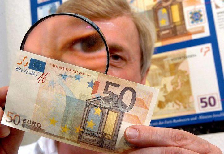 Klaus-Dieter Ehling, experto en falsificaciones de dinero, examina con lupa un billete falso de 50 euros en Rampe, Alemania. (Archivo/EFE)