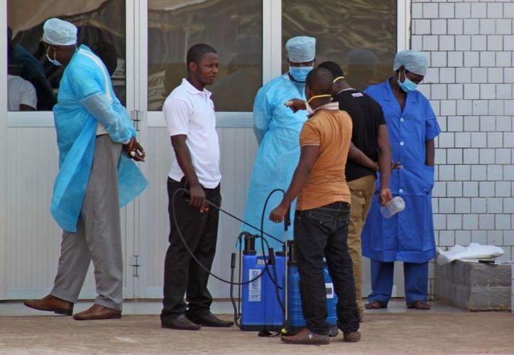 Imagen de personal médico a la entrada de un hospital, tras recibir a pacientes sospechosos de tener ébola en Guinea. (Agencias)