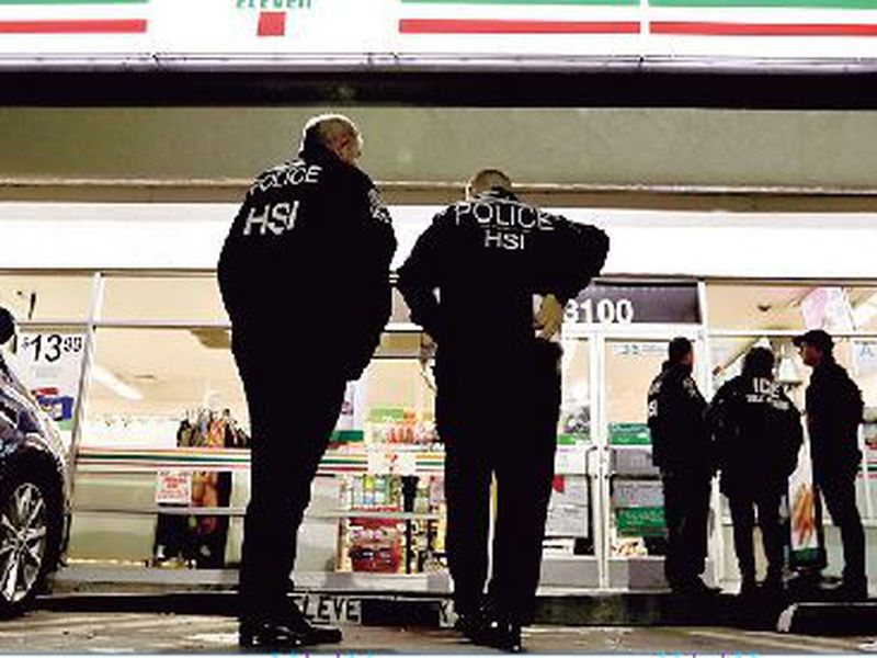 U.S. Immigration and Customs Enforcement agents serve an employment audit notice at a 7-Eleven convenience store in Los Angeles.