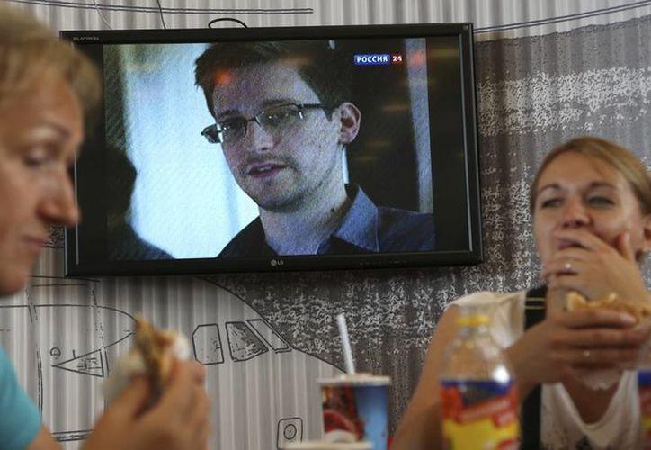 Los pasajeros en el aeropuerto de Moscú comen mientras difunden por televisión un programa de noticias que muestra un informe sobre Edward Snowden. (Agencias)