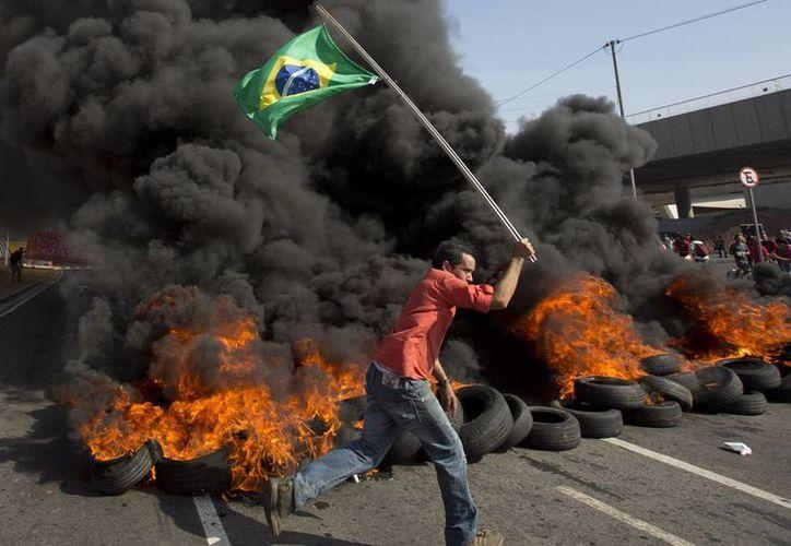 Quema de llantas en Sao Paulo. Cientos de civiles llegaron para exigir al gobierno invertir más dinero en vivienda. (Foto: AP)