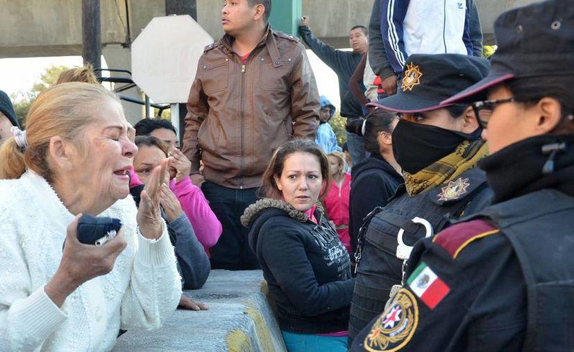 Familiares de los internos frente a la policía fuera de la prisión de Topo Chico, donde estalló un motín y en que fallecieron 49 personas. (Agencias)