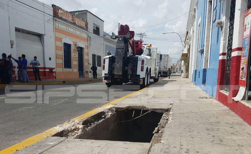 Un tráiler que intentó dar vuelta en una esquina del Centro de Mérida se quedó atorado, debido a que una de las llantas traseras se subió a la banqueta y rompió un registro. (Cristian Cuxín/SIPSE)