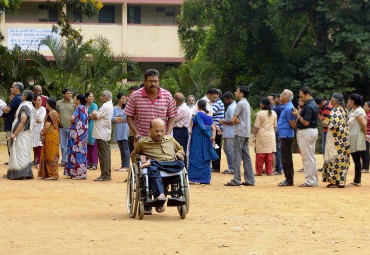 Votantes indios hacen fila para votar hoy, durante una de las fases de las elecciones generales de la India en Bangalore. (EFE)