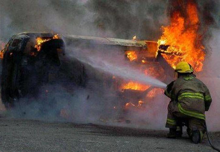 Brigadistas de protección civil lograron apagar las llamas de los vehículos incendiados. (Milenio)