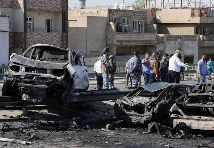 Cuerpos de seguridad inspeccionan el área en donde un coche bomba explotó y mató a varias personas, en Nueva Bagdad, Bagdad, Irak. (AP)