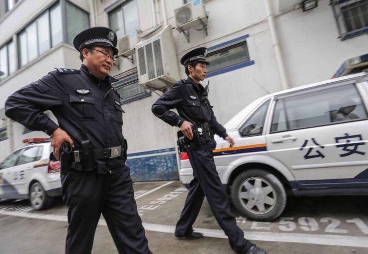 Dos policías patrullan por una calle de Shanghai. (Archivo/EFE)