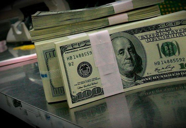 El policía descubrió 65 fajos de efectivo escondidos en el vehículo. (miled.com)