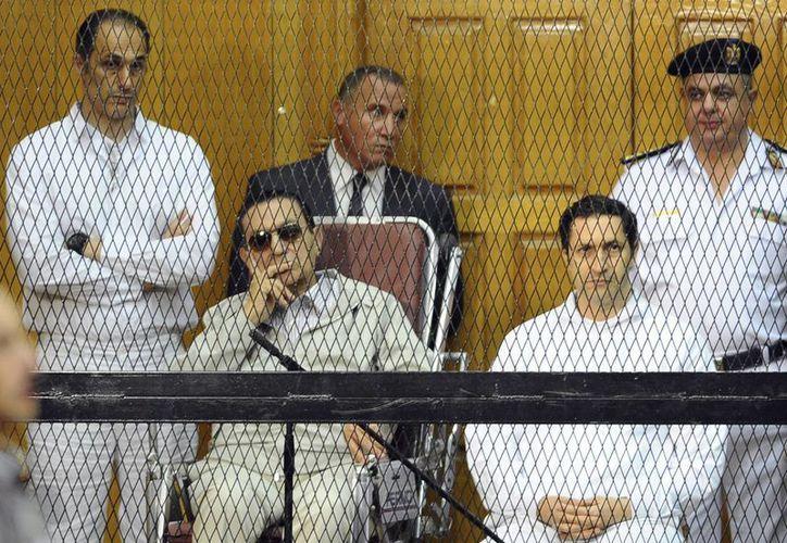 En esta foto del 14 de septiembre del 2013 se ve al expresidente egipcio Hosni Mubarak, sentado a la izquierda, y sus dos hijos Gamal Mubarak, izq., y Alaa Mubarak en un juicio en El Cairo. (Foto de archivo: AP/Mohammed al-Law)