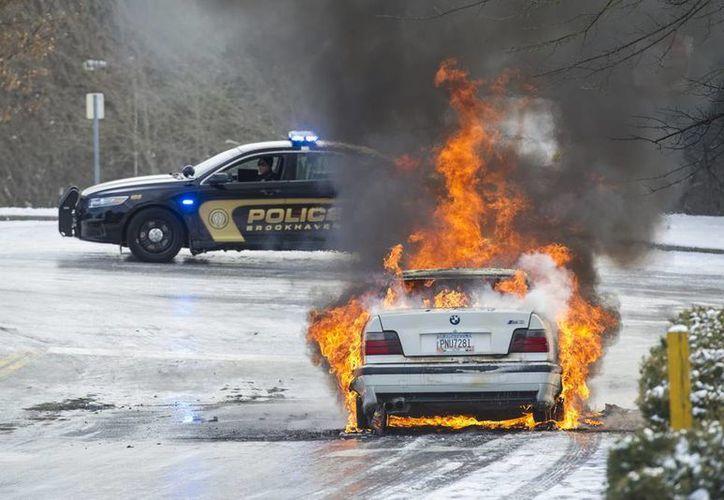 La policía 'custodia' un vehículo incendiado en una carretera de Georgia, EU. Cientos de conductores se vieron obligados a abandonar sus autos en las carreteras porque éstas eran intransitables, a causa del clima. (Agencias)