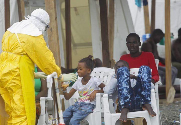 Un trabajador de salud da de beber a un niño enfermo de ébola, en el Centro de Tratamiento de MSF en Monrovia, Liberia. (Archivo/EFE)
