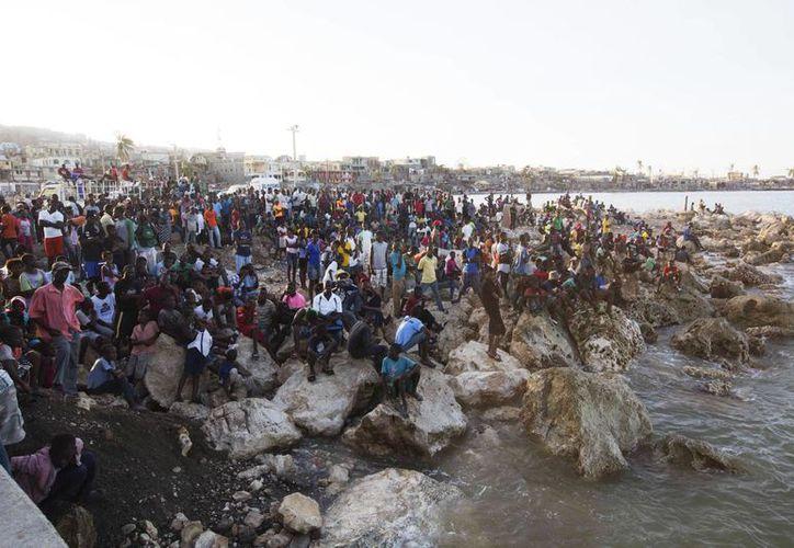 """Imagen de los residentes esperan en la costa como un bote con agua y comida de la """"Misión de Esperanza"""" caridad llega después del huracán Mateo se extendió por Jeremie, Haití, el sábado 8 de octubre de 2016. Jeremie parece ser el epicentro de la creciente crisis humanitaria del país en a raíz de la tormenta. (Foto AP / Dieu Nalio Chery)"""