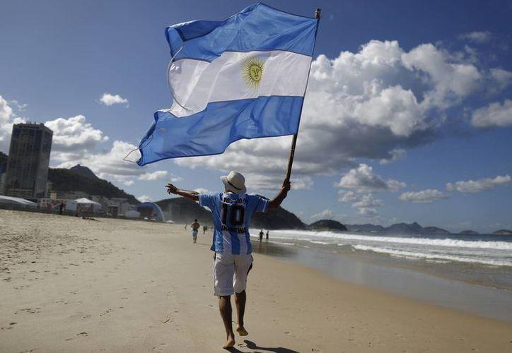 El control de los argentinos en Brasil es difícil, pues no necesitan tener visa para quedarse. En la imagen un seguidor de la selección de futbol argentina ondea una bandera de su país. (AP)