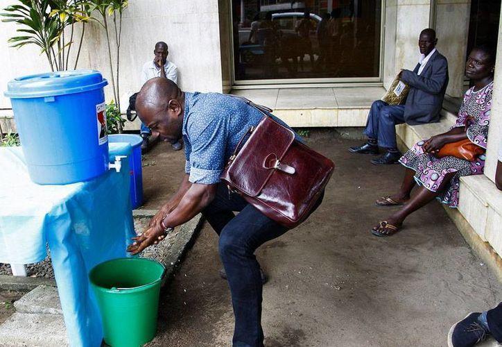El Gobierno de Sierra Leona aprobó una ley para evitar que familiares, amigos o conocidos de enfermos de ébola escondan información sobre los pacientes. En la foto, un ciudadano de Costa de Marfil se asea, como medida preventiva para evitar el contagio. (Contexto/Efe)