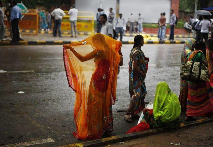 Una mujer india ajusta su sari después mojarse en la lluvia, en Nueva Delhi, India. (Agencias)