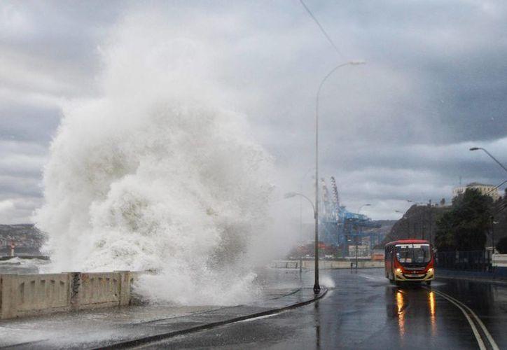 Fotografía donde se observan fuertes olas, este sábado 8 de agosto de 2015, en la costa de la región de Valparaíso, Chile. Se reporta la muerte de seis personas y  y cuantiosos daños materiales. (EFE)