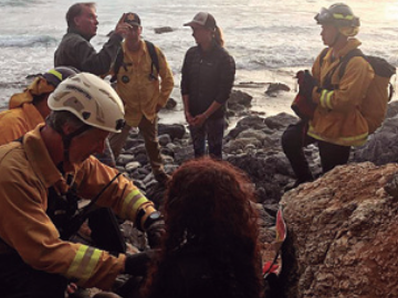 Authorities tend to Angela Hernandez, foreground center, after she was rescued, in Morro Bay, Calif.