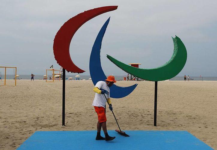 Un hombre limpia una alfombra en la playa de Copacabana, antes de la presentación de la escultura de los Juegos Paralímpicos, que está hecha de plástico reciclado y tiene 4 metros de alto por 3 metros de largo. (EFE)