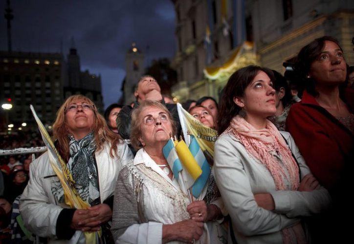 Mirando en cuatro pantallas gigantes instaladas fuera de la Catedral Metropolitana, en la Plaza de Mayo, muchos argentinos pasaron la noche entera en vigilia. (Agencias)