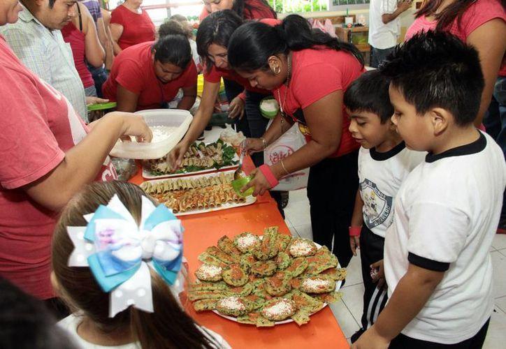 Enseñan a padres de familia e hijos a cómo elaborar comida nutritiva de acuerdo al 'Plato del bien comer maya'. (Milenio Novedades)