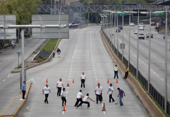 Empleados de una fábrica juegan futbol soccer en plena avenida, cerca del Aeropuerto Benito Juárez, en el DF., en el marco de los bloqueos de maestros.  (Agencias)
