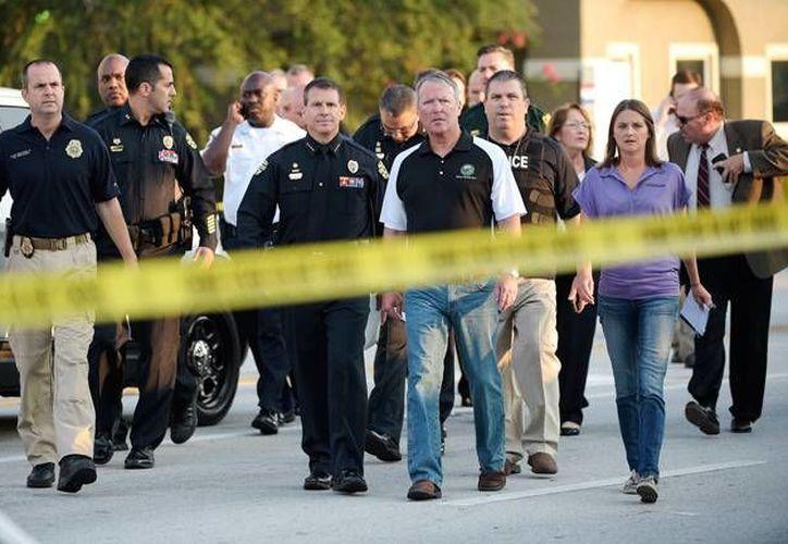 Policías preventivos e investigadores llegan al club nocturno donde la madrugada de este domingo un hombre abrió fuego contra los asistentes y mató a 20 personas. (AP)