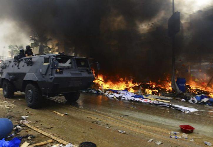 Tiendas de campaña arden junto a vehículos blindados de la policía en el campamento de los seguidores de Mursi en la plaza de Rabea al Adauiya en El Cairo. (EFE)