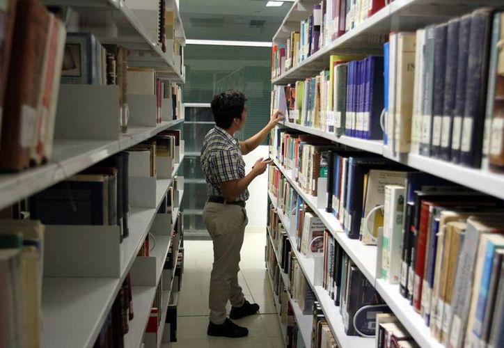 La consulta de libros favorece la investigación de estudiantes. imagen de una persona en su búsqueda de algún ejemplar. (Milenio Novedades)