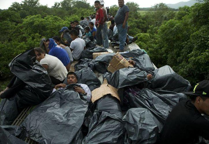 Inmigrantes centroaméricanos en el techo de un tren de carga. (Archivo/AP)