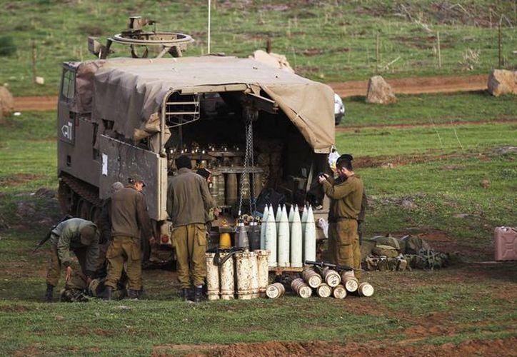 Soldados israelíes junto a varias piezas de artillería en los Altos del Golán cerca de la frontera con Siria, esta madrugada. (EFE)