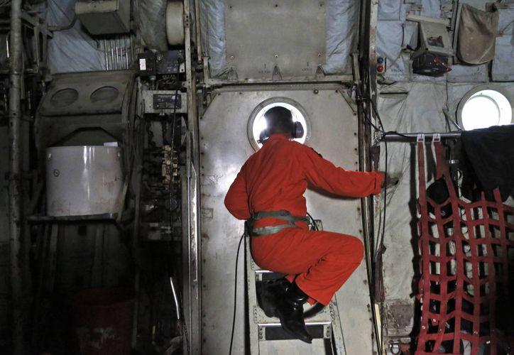 Un tripulante de un avión C-130 de la fuerza aérea indonesia, del 31ro escuadrón aéreo, mira por la ventana durante una operación de búsqueda del Vuelo 8501 de Air Asia en aguas del estrecho de Karimata, Indonesia. (Agencias)