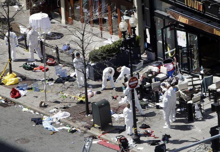 Expertos revisan este martes minuciosamente una de las áreas donde explotó una de las bombas ayer en Boston. (AP)