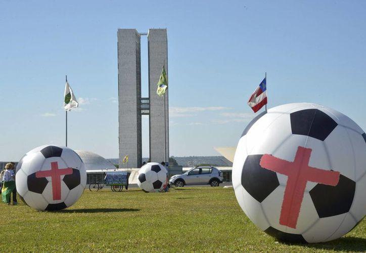 La organización no gubernamental Río de Paz lanza doce balones de dos metros de diámetro en Brasilia, para protestar contra el Mundial de fútbol y exigir que el Gobierno 'pida perdón' por el gasto público en el evento de la FIFA. (EFE)
