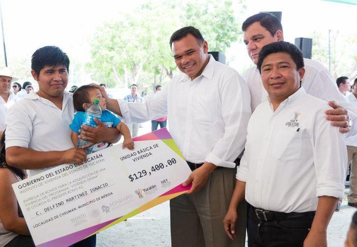 El gobernador Rolando Zapata Bello entrega un bono de vivienda a una familia beneficiada. (SIPSE)