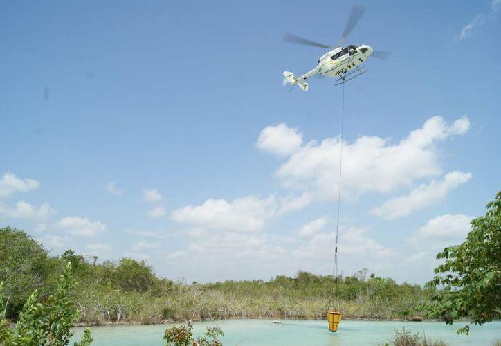 Los helicópteros que estarán bajo resguardo de la Conafor cuenta con una helibalde con una capacidad de mil 200 litros, para realizar descargas de agua y disminuir la intensidad del fuego. (Juan Palma/SIPSE)