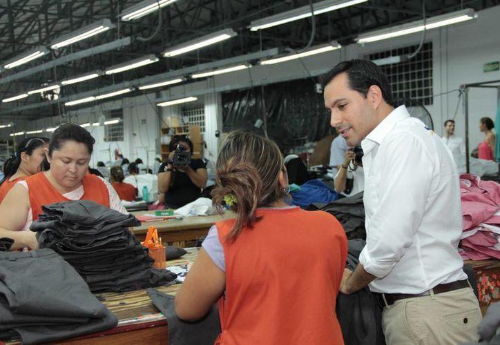 Mauricio Vila, candidato del PAN a la alcaldía de Mérida, platica con empleados de una fábrica de ropa. (SIPSE)