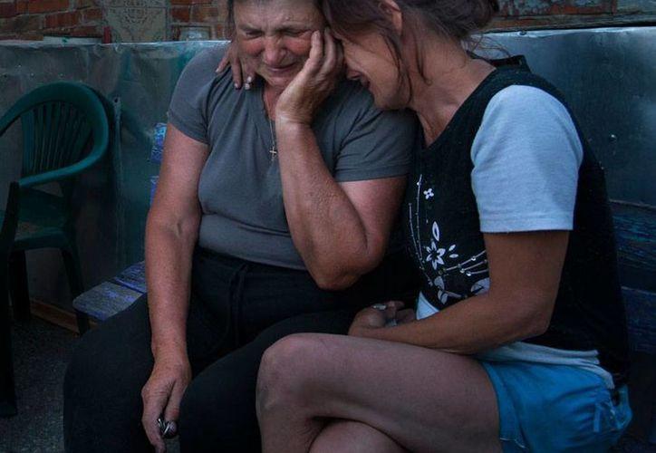 Las elecciones presidenciales en Ucrania estarán 'pasadas por lluvia... de balas': el conflicto armado entre prorrusos y fuerzas de seguridad no se detendrá. Imagen de dos deudos de víctimas de un atentado. (Foto de contexto/AP)