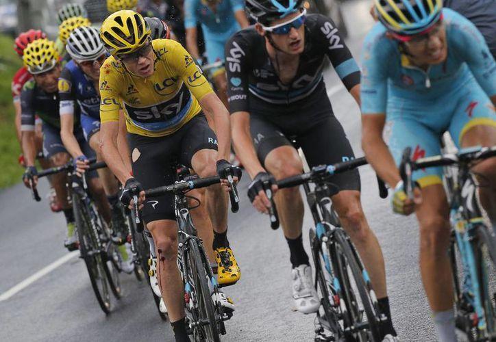 Fabio Aru, de Italia, y Wouter Poels, de Holanda, pedalean por delante del británico Chris Froome, quien sufrió una caída y sin embargo mantuvo el liderato del Tour de Francia. (AP)
