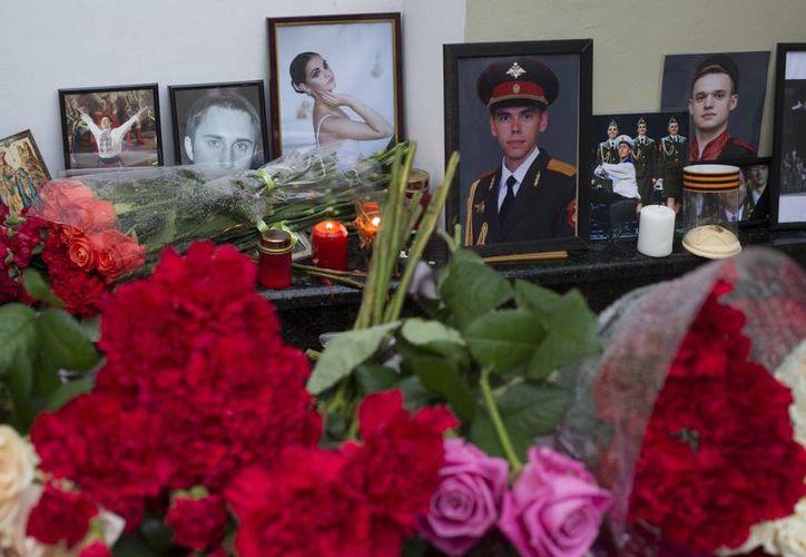 Retratos de miembros del Alexandrov Ensemble, que viajaban en el avión que se estrelló en el Mar Muerto, fueron colocados delante del edificio Alexandrov Ensemble en Moscú, Rusia. (AP/Ivan Sekretarev)