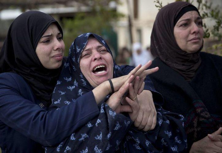 Mujeres palestinas lloran durante el funeral de Yehya Taha, de 21 años, quien murió durante enfrentamientos con soldados israelíes tras una redada militar israelí en la ciudad cisjordana de Qattana. (Agencias)