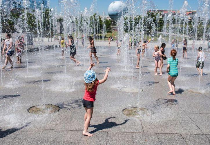 Niños juegan en las fuentes de la plaza André Citroen en París, 30 de junio de 2015. Una masa de aire caliente desde Africa provoca temperaturas inusualmente altas en Europa. (AP Photo/Kamil Zihnioglu)