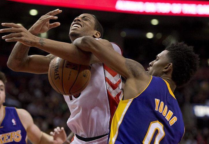 DeMar DeRozan (i) recibe una falta de Nick Young, de Lakers, en el último cuarto del partido entre los cuadros de Toronto y Los Angeles. (Agencias)