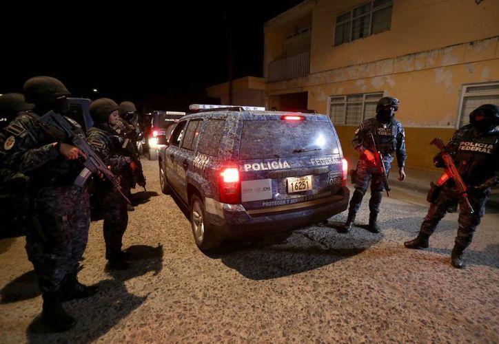 Policías Federales inspeccionan uno de sus vehículos perforados por las balas. (EFE)