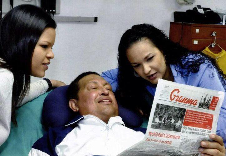 El presidente de Venezuela, Hugo Chávez, junto a sus hijas Rosa Virginia (d) y María Gabriela (i) leyendo el diario cubano Gramna. (EFE)