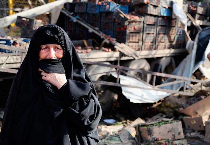 Un atentado dejó al menos 62 muertos en un mercado de Bagdad. En la imagen, una mujer pasa cerca del sitio de la explosión. (AP)