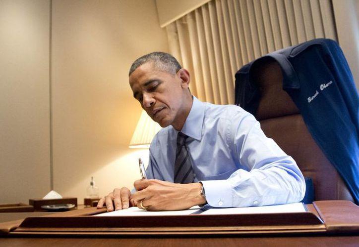 El presidente Barack Obama al momento de firmar dos documentos presidenciales relacionados con sus acciones en materia de inmigración en EU. (Agencias)
